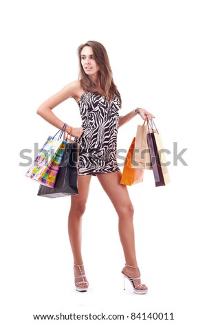 Full length of a happy young woman holding shopping bags over white background - stock photo