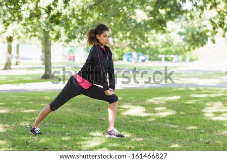 Full length of a healthy young woman doing stretching exercise in the park - stock photo