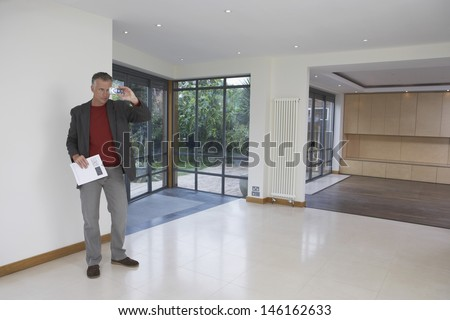 Full length of a male real estate agent photographing new property - stock photo