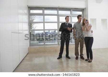 Full length of a male real estate agent showing couple new apartment as woman photographs - stock photo