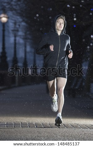 Full length of a male runner on early winter morning in London - stock photo