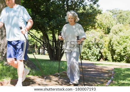 Full length of a mature couple Nordic walking on pathway in the park - stock photo