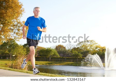 Full length of a mature man jogging with fountain in background. Horizontal shot. - stock photo