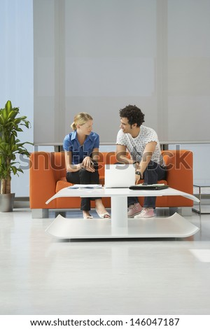 Full length of a multiethnic couple using laptop on orange sofa in reception room at office - stock photo