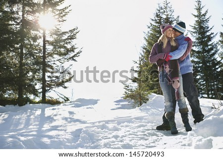 Full length of a romantic couple standing on snow covered hill - stock photo