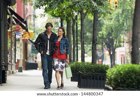 Full length of a smiling couple walking on sidewalk - stock photo