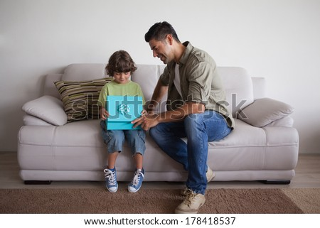 Full length of a smiling father and son with gift box sitting on sofa in the living room at home - stock photo