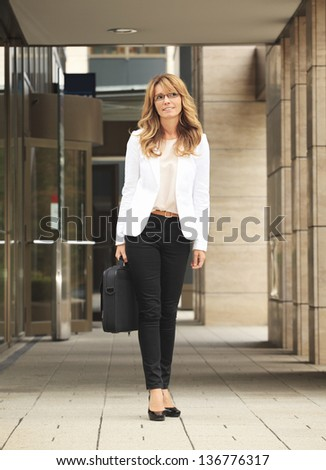 Full length of a smiling mature businesswoman walking on street - stock photo