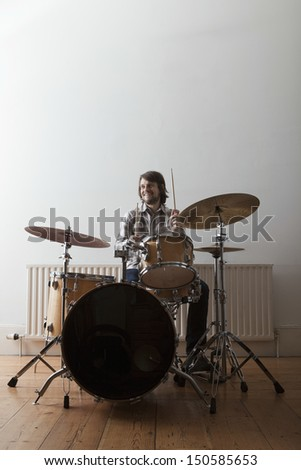 Full length of a smiling young man playing drum set on wooden floor - stock photo