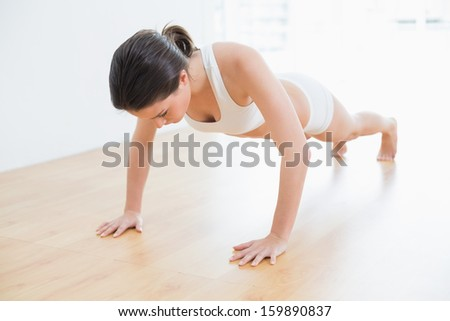 Full length of a sporty young woman doing push ups in fitness studio - stock photo