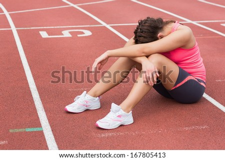 Full length of a tensed sporty woman sitting on the running track - stock photo