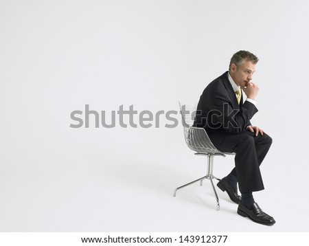 Full length of a thoughtful businessman sitting in chair against gray background - stock photo