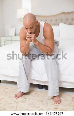 Full length of a thoughtful young bald man sitting on bed at home - stock photo