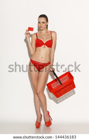 Full length of a woman in red bikini holding empty shopping basket and showing blank credit card, against white background - stock photo