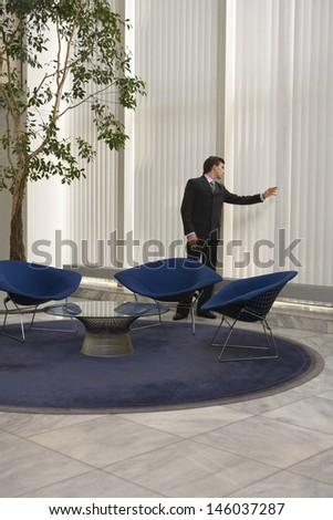 Full length of a young businessman looking out of window in office lobby - stock photo
