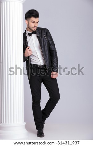 Full length of a young casual business man looking away from the camera while leaning on a white colum - stock photo