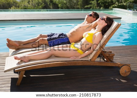 Full length of a young couple resting on sun loungers by swimming pool - stock photo