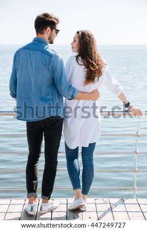 Full length of a young couple standing backwards hugging and looking at each other at the seaside - stock photo