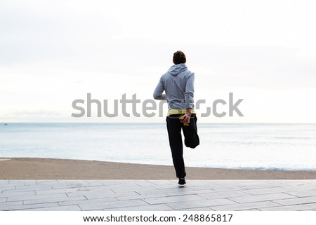 Full length of a young jogger stretching in the morning and admiring beautiful view while standing on the beach - stock photo