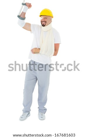 Full length of a young man in hard hat with broken hand and crutch over  white background - stock photo