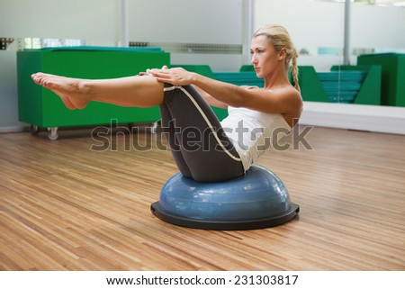 Full length of a young woman doing fitness exercise in fitness studio - stock photo
