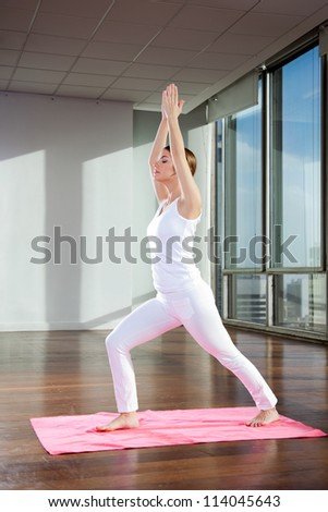 Full length of a young woman performing Crescent Moon pose on mat - stock photo