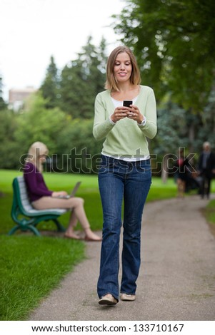 Full length of a young woman reading text message as she walks in park - stock photo