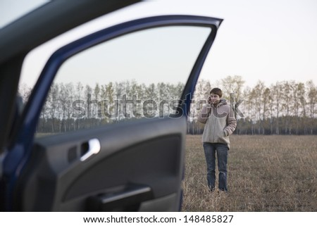 Full length of a young woman using mobile phone near car in field - stock photo