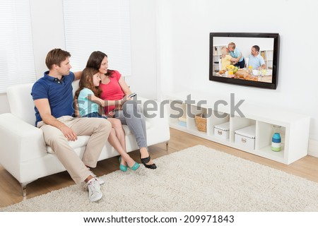 Full length of affectionate family watching TV together at home - stock photo