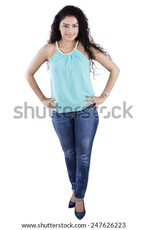Full length of attractive woman with curly hair standing in the studio, isolated on white - stock photo