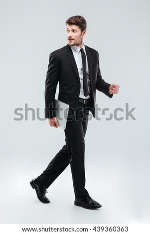 Full length of attractive young businessman walking and holding laptop over white background - stock photo