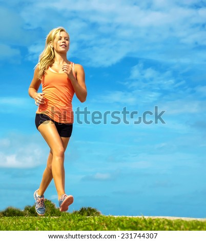 Full length of attractive young female athlete jogging on sidewalk at beach - stock photo