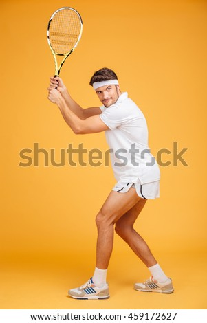 Full length of attractive young man tennis player standing and playing tennis over yellow background - stock photo