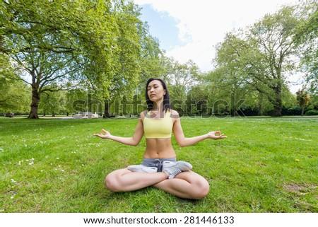 Full length of beautiful fit woman performing yoga at park - stock photo