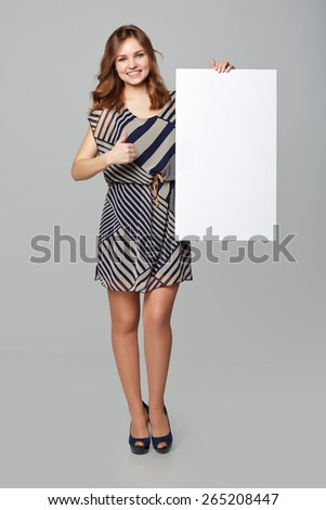 Full length of beautiful woman behind, holding white blank advertising board banner and showing an approval sign, on gray background - stock photo