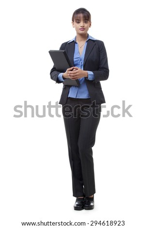 Full length of beautiful young executive holding laptop over white background - stock photo