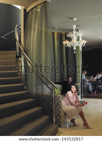 Full length of beautiful young woman sitting on couch in hotel lobby - stock photo