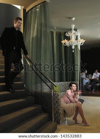 Full length of beautiful young woman waiting in hotel lobby with man descending staircase - stock photo