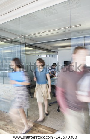 Full length of blurred office workers leaving conference room - stock photo