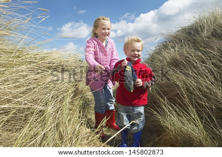 Full length of brother and sister standing among long grass - stock photo