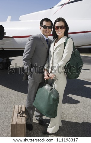 Full length of business couple standing together with luggage at airfield - stock photo