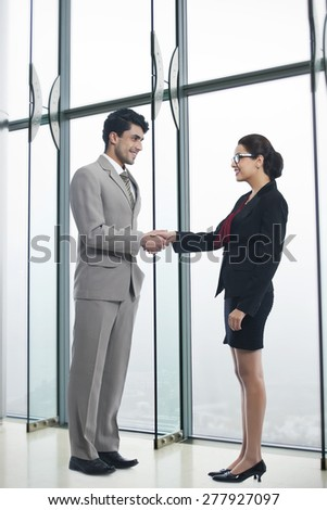 Full length of business people shaking hands in office - stock photo