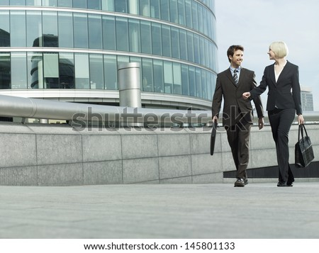 Full length of businessman and businesswoman walking outside office building - stock photo
