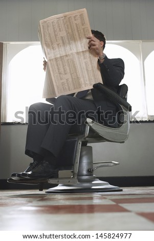 Full length of businessman reading newspaper while waiting for haircut in hair salon - stock photo