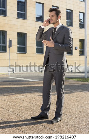 Full length of businessman using cell phone against office building - stock photo