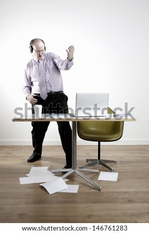 Full length of businessman wearing headphones while playing air guitar at office desk - stock photo