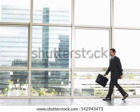 Full length of businessman with briefcase walking in office building - stock photo