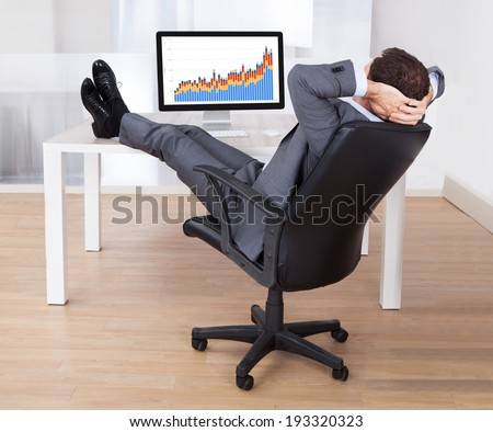 Full length of businessman with feetup relaxing at computer desk in office - stock photo