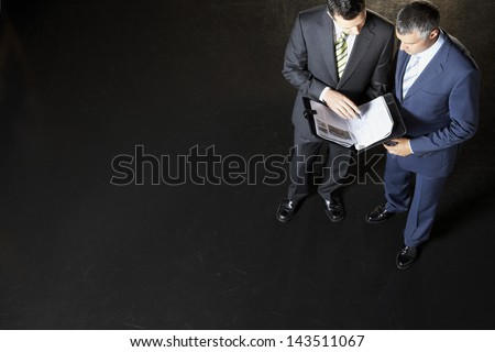 Full length of businessmen reviewing documents against dark background - stock photo