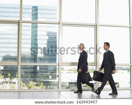 Full length of businessmen with briefcases walking in office building - stock photo